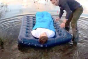 Terrible friend drags his mate`s blow-up mattress into a lake while he`s sleeping on it, films him wake up surrounded by water!
