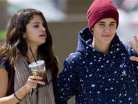 Bieber and Selena one with baggy pant and one with ripped-jean running away from paparazzi
