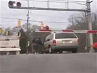 Man gets out of a mini-van just in time before a train hits it.