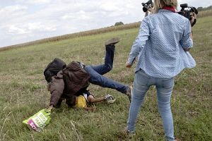 Hungarian camerawoman fired after kicking a little girl and tripping up a migrant father carrying his terrified young child as they fled police!