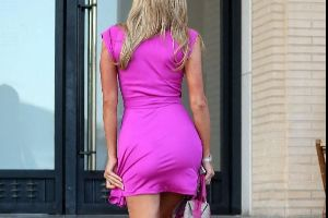 Sexy Barbie! Paris Hilton shows off her curves in a pink mini dress that matches with her pink Bentley